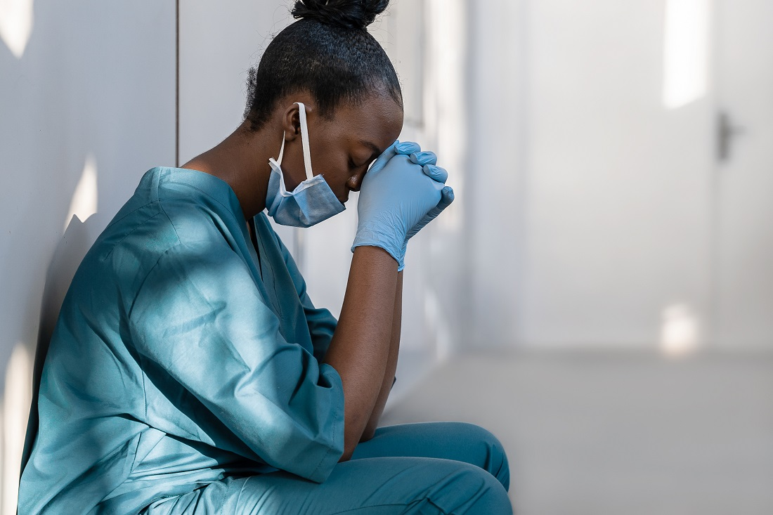 Tired depressed female african nurse wearing face mask sits on hospital floor.