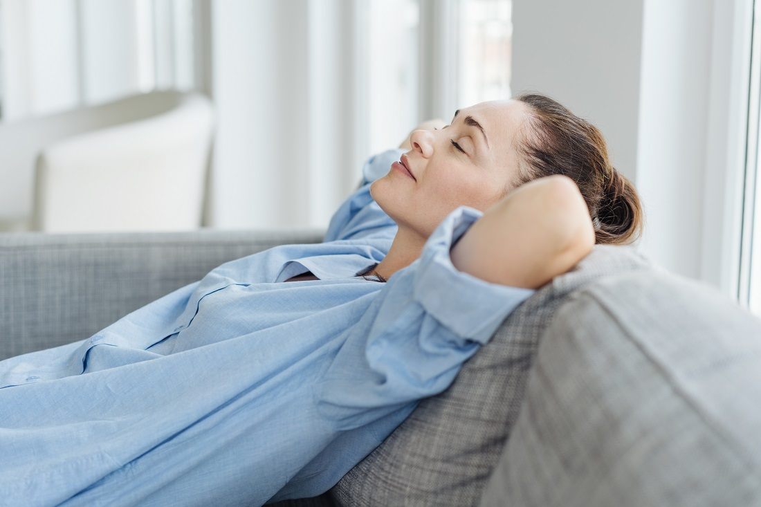 Exhausted young woman relaxing on a sofa