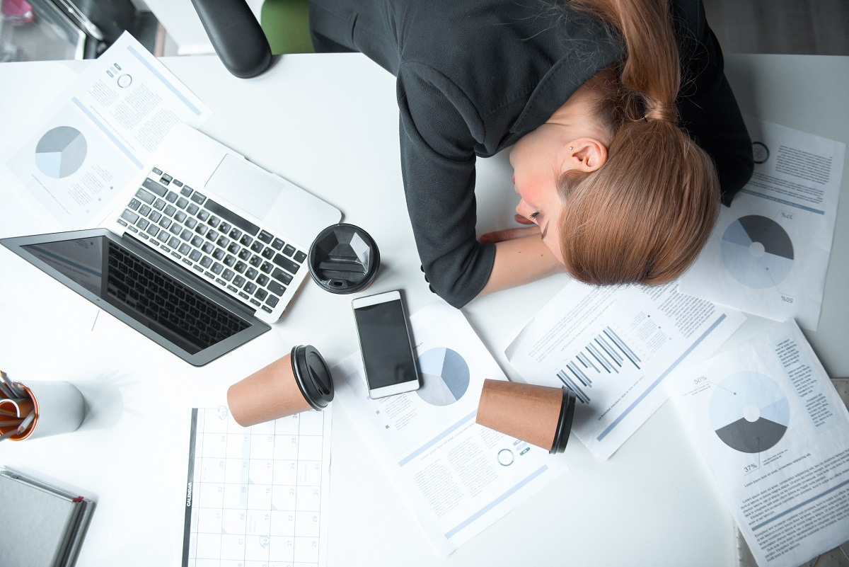 Serious tired businesswoman sleeping on table